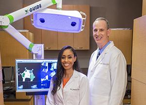 Doctors next to x-ray machine.
