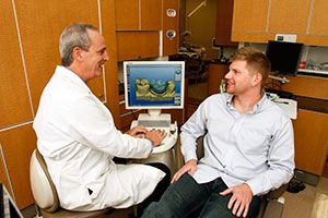 Dr. Robert Schmidt with patient and using CEREC machine.