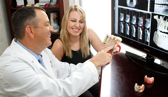 Doctor showing patient model of teeth and implants.