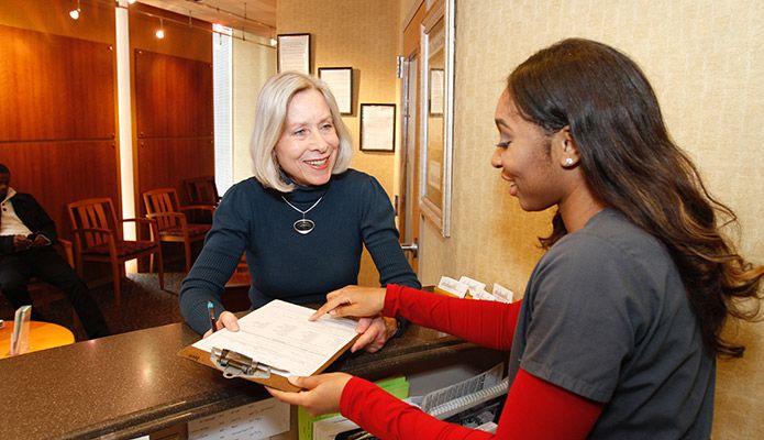 Staff handing patient papers.