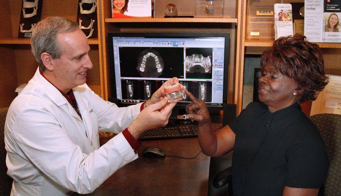 Doctor showing patient model of teeth.